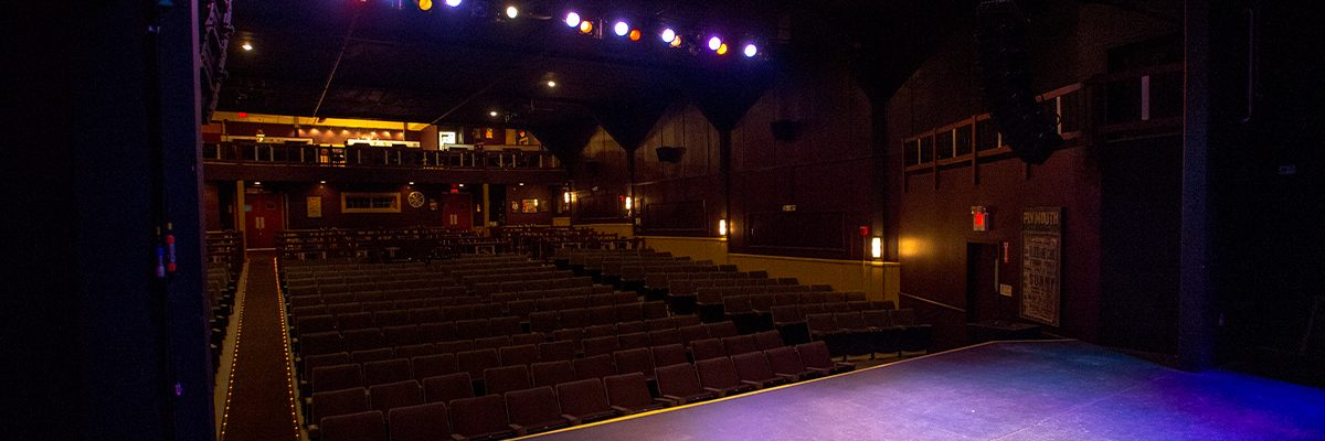 view from stage lit in purple facing the seats