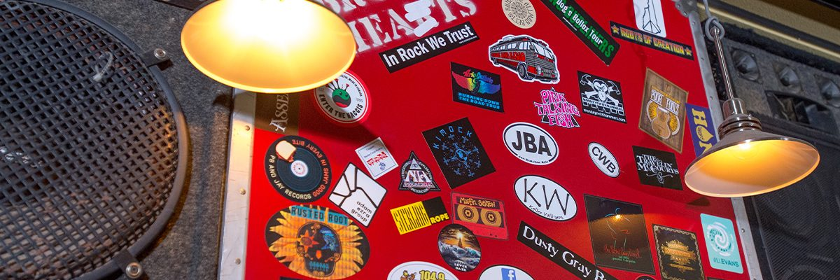 close up of band stickers on sound box above bar
