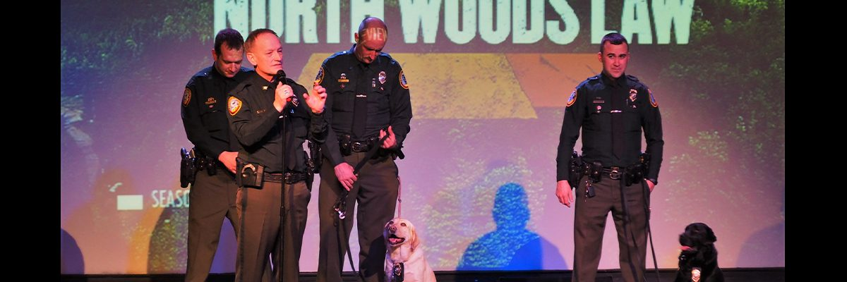 north woods law on stages with canines hosting an event